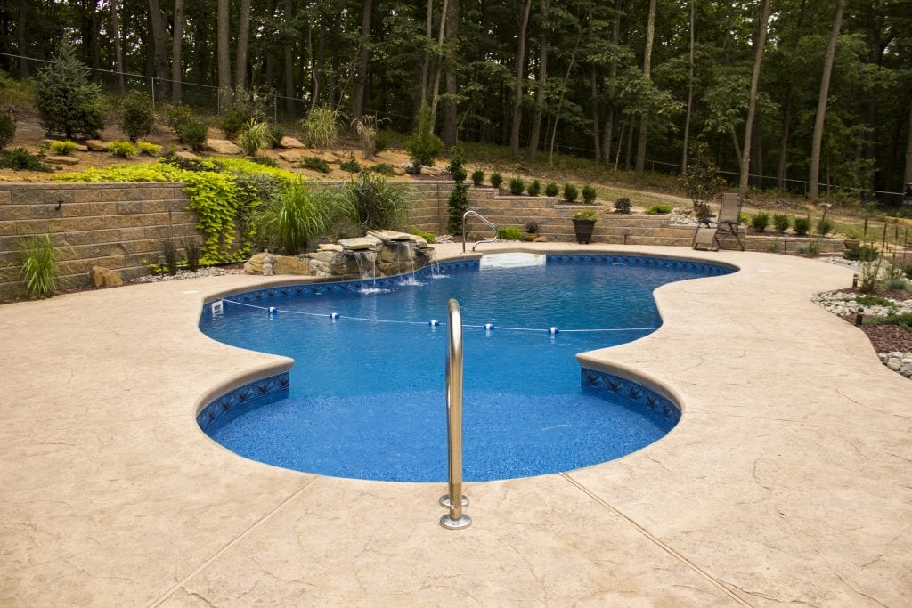 blue lagoon with waterfall and architectural stamped concrete